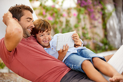 Buy stock photo Shot of a young boy and his father bonding outdoors