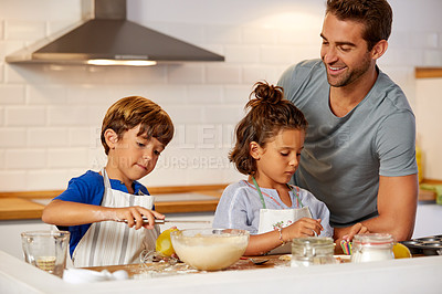 Buy stock photo Cropped shot of a father helping his son and daughter bake in the kitchen at home