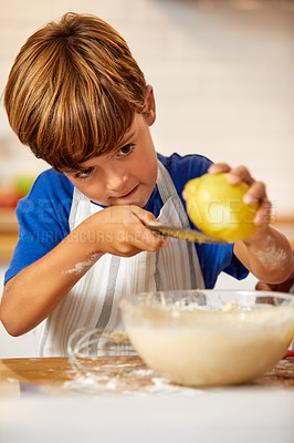 Buy stock photo Cropped shot of a little boy grating lemon zest into batter in the kitchen at home