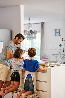 Buy stock photo Rearview shot of a father helping his son and daughter bake in the kitchen at home