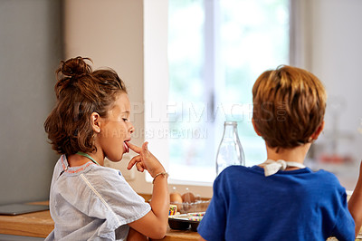 Buy stock photo Rearview shot of a young brother and sister tasting batter in the kitchen at home