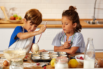 Buy stock photo Cropped shot of a brother and sister spooning batter into a muffin tin in the kitchen at home