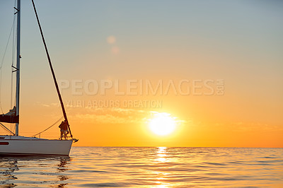 Buy stock photo Shot of a young couple going for an ocean cruise at sunset