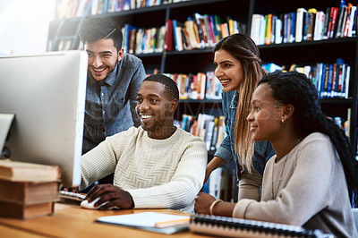Buy stock photo Shot of a group of young students using a computer together in a college library