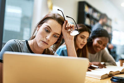 Buy stock photo Shot of a young woman using a laptop in a college library and looking stressed