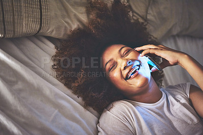 Buy stock photo Shot of a young woman talking on a cellphone in bed at night