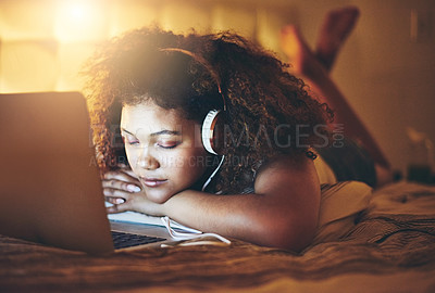 Buy stock photo Shot of a young woman sleeping on her bed in front of a laptop at home