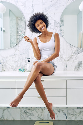 Buy stock photo Shot of an attractive young woman about to brush her teeth in the bathroom at home