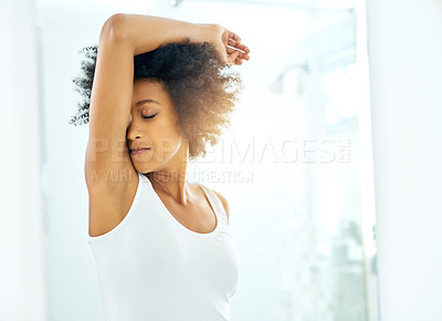Buy stock photo Cropped shot of an attractive young woman smelling her armpits at home