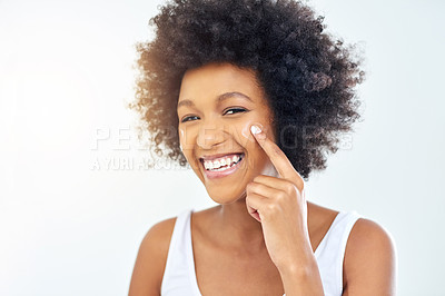 Buy stock photo Cropped shot of an attractive young woman applying moisturizer on her face in the bathroom at home