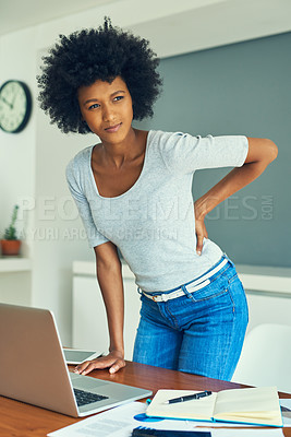 Buy stock photo Cropped shot of an attractive young businesswoman suffering from back pain while working at home
