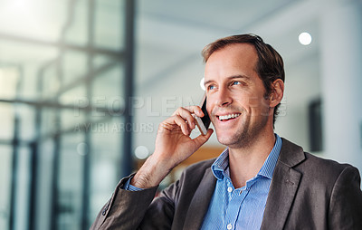 Buy stock photo Shot of a handsome young businessman using a phone in a modern office