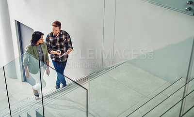Buy stock photo Shot of two young coworkers using a digital tablet while walking up stairs in a modern office