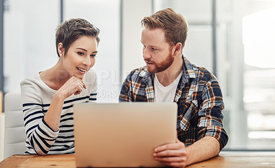 Buy stock photo Shot of two young coworkers using a laptop together in a modern office