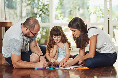 Buy stock photo Shot of a mother and father drawing together with their young daughter at home