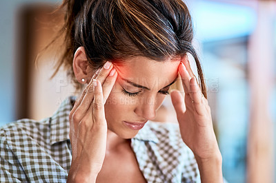 Buy stock photo Shot of a uncomfortable looking woman holding her head in discomfort due to pain at home during the day