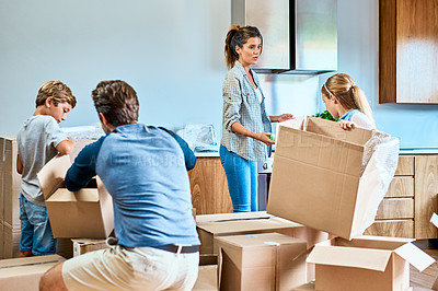 Buy stock photo Shot of a focused young family working together and unpacking boxes out in their new home inside during the day