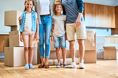 Buy stock photo Portrait of a young brother and sister standing next to their unrecognizable parents inside at home during the day