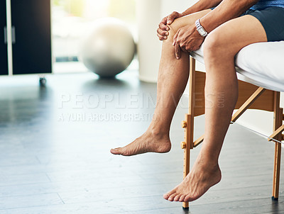 Buy stock photo Cropped shot of an unrecognizable man sitting on a bed during his physiotherapy