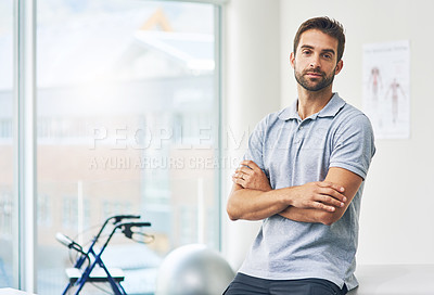 Buy stock photo Cropped portrait of a male physiotherapist sitting with his arms folded in his office