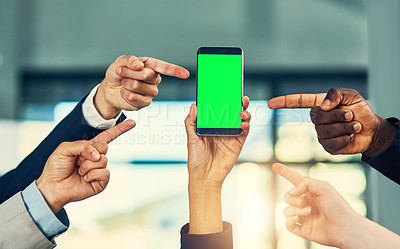 Buy stock photo Cropped shot of a group of businesspeople pointing at the green screen of a mobile phone in a modern office