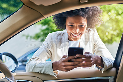 Buy stock photo Shot of a cheerful young businesswoman browsing on her cellphone while on her way to get into her car to go to work