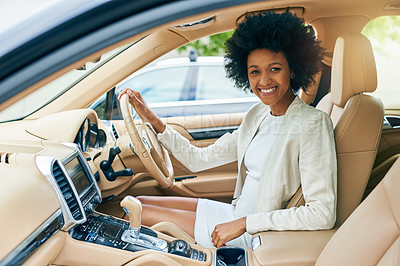 Buy stock photo Portrait of a cheerful young businesswoman seated in the driver seat of a car on her way to work during the day