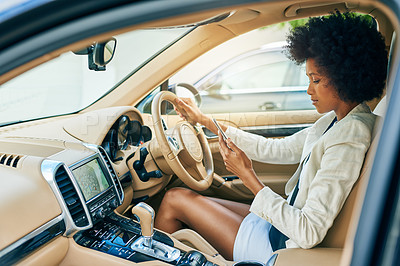 Buy stock photo Shot of a focused young businesswoman driving in a car while browsing on her mobile phone during the day