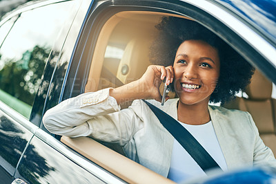 Buy stock photo Shot of a cheerful young businesswoman driving in a car on her way to work while talking on a cellphone during the day