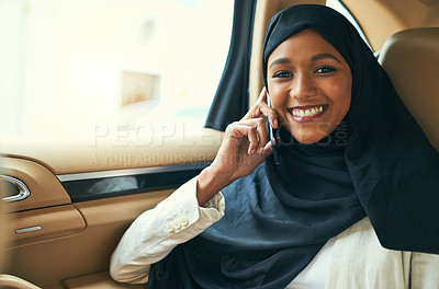 Buy stock photo Portrait of a cheerful young businesswoman talking on her mobile phone while being seated in the back of a car on her way to work