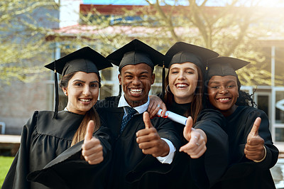 Buy stock photo Portrait of a group of young students showing thumbs up on graduation day