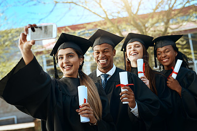 Buy stock photo Portrait of a group of students taking selfies with a mobile phone on graduation day