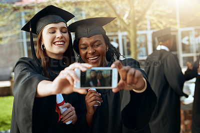 Buy stock photo Shot of two young women taking selfies with a mobile phone on graduation day