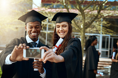 Buy stock photo Shot of a young man and woman taking selfies with a mobile phone on graduation day