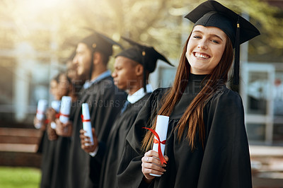 Buy stock photo Portrait of a young woman holding her diploma while standing with her fellow students on graduation day