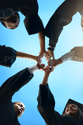 Buy stock photo Low angle shot of a group of young students joining their hands together on graduation day