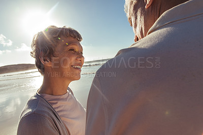 Buy stock photo Shot of a happy mature couple enjoying a day at the beach