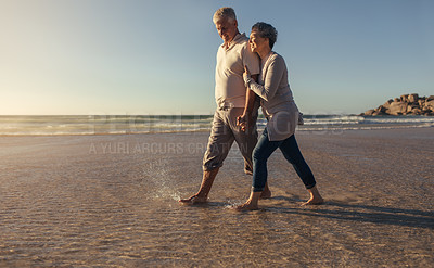 Buy stock photo Shot of a happy mature couple going for a relaxing walk on the beach