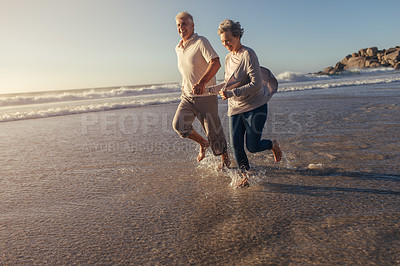 Buy stock photo Shot of a happy mature couple having fun at the beach