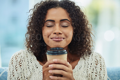Buy stock photo Shot of an attractive young woman enjoying a cup of coffee at home