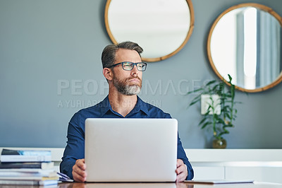 Buy stock photo Shot of a confident middle aged businessman working on his laptop while looking into the distance and contemplating at home during the day