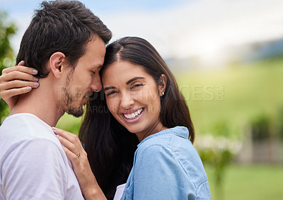 Buy stock photo Cropped shot of an affectionate young couple embracing while standing outdoors