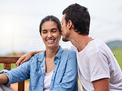 Buy stock photo Cropped shot of an affectionate young couple sitting on a bench outdoors