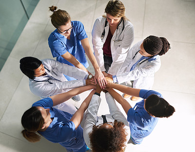 Buy stock photo High angle shot of a group of medical practitioners joining their hands together in a huddle