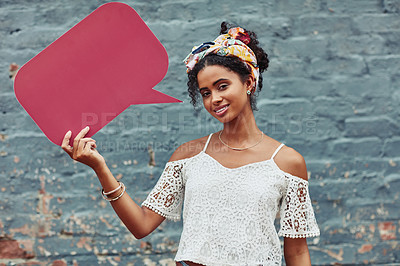 Buy stock photo Cropped shot of an attractive young woman holding a speech bubble against a brick wall outside