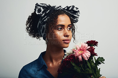 Buy stock photo Studio shot of an attractive young woman holding a bunch of flowers against a grey background