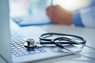 Buy stock photo Closeup shot of a stethoscope resting on a laptop with an unrecognizable doctor working in the background