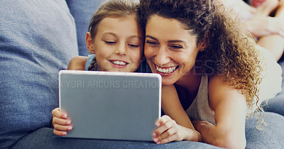 Buy stock photo Shot of a cute little girl using a digital tablet with her mother on the sofa at home