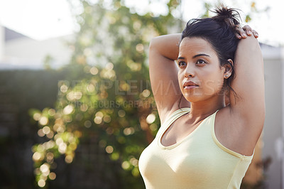 Buy stock photo Shot of a beautiful young woman warming up before a workout at home