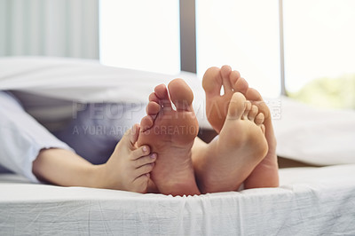 Buy stock photo Shot of a unrecognizable couple's feet touching each other while they sleep in bed during morning hours